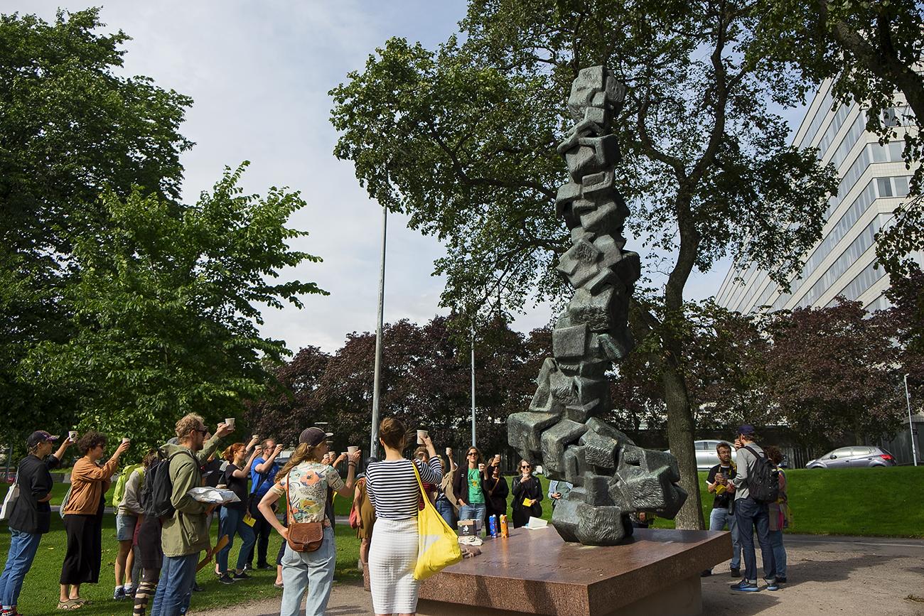 People raiding their glasses at the Miina Sillanpää monument